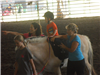 Little Kid riding a horse with women assisting it