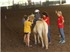 Child riding a horse with women walking it around the arena