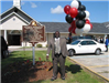 Pastor Holding balloons in front of the sign