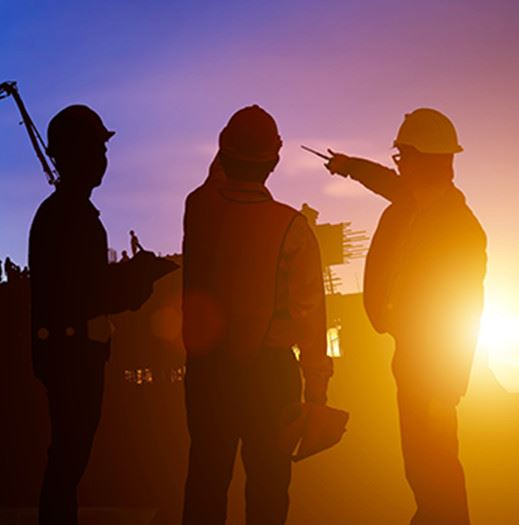 Three people on a construction site with sun setting in the distance