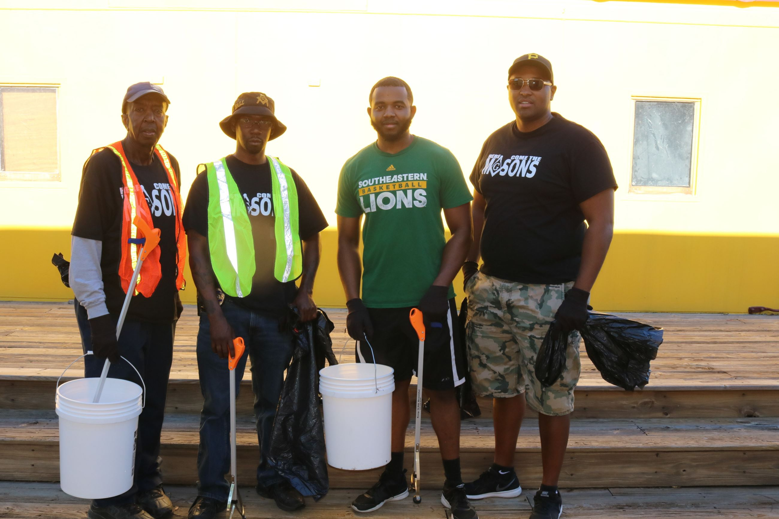 Four men pose together during the clean up event